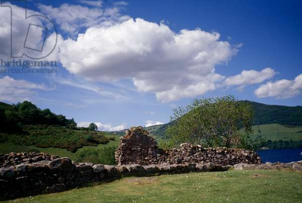 A crumbling wall stands on green hills on Urquhart Castle grounds (photo)