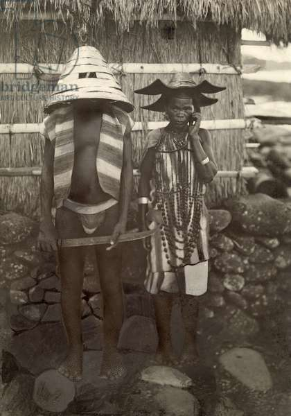 An Atayal chief in head-hunting raid attire stands next to his wife, Taiwan, 1920 (b/w photo)