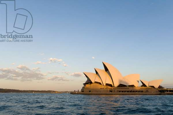 A view of the Sydney Opera House from across the harbor at sunset (photo)