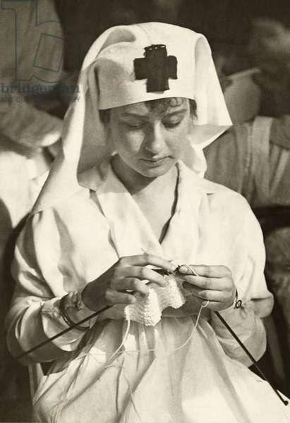 A World War I era American Red Cross nurse knitting, 1917 (b/w photo)