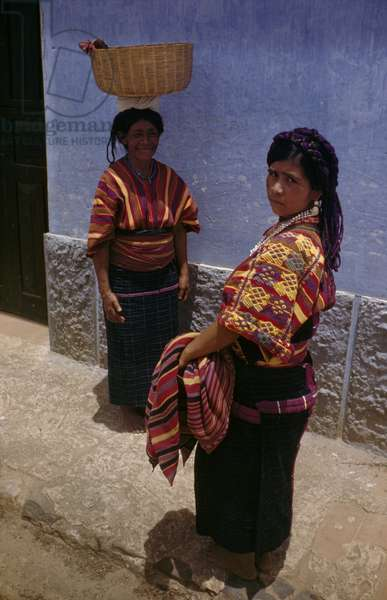 Women in brightly colored woven shirts pose near a building, San Juan Sacatepequez, Guatemala, 1947 (photo)