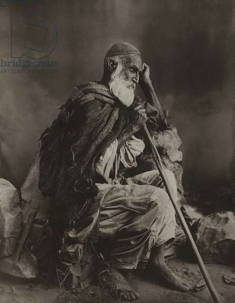 Portrait of a Pashtun tribesman holding a walking stick (b/w photo)