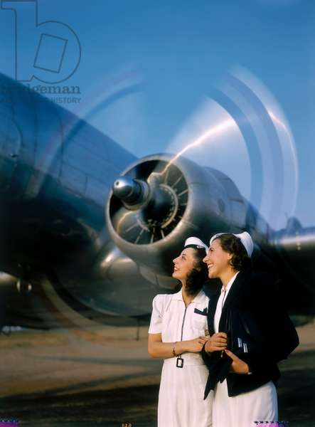 Two young women stand near a turning aircraft propeller, NA, 1940 (photo)