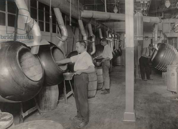 Workers filling barrels with pills to be coated, Massachusetts, 1920 (b/w photo)