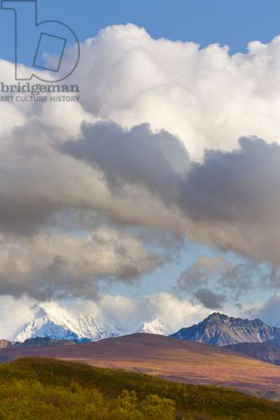Cumulus clouds over snow capped Alaska range and autumn tundra (photo)
