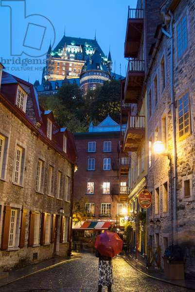 The iconic Chateau Frontenac dominates the skyline of Quebec City above shops and houses on a cobble stoned street