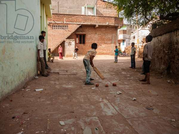 Muslim and Hindu boys play cricket on a dirt lane in the village of Napa where Mahatma Ghandi passed through during his Salt March (photo)