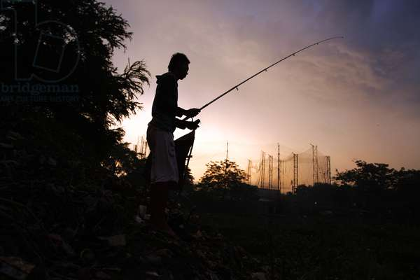 A man fishes at sunset (photo)