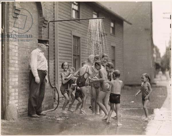 Children cool off from summer heat under a sidewalk spray outside a Connecticut firehouse, Near Housatonic River, Connecticut, USA, 1935 (b/w photo)