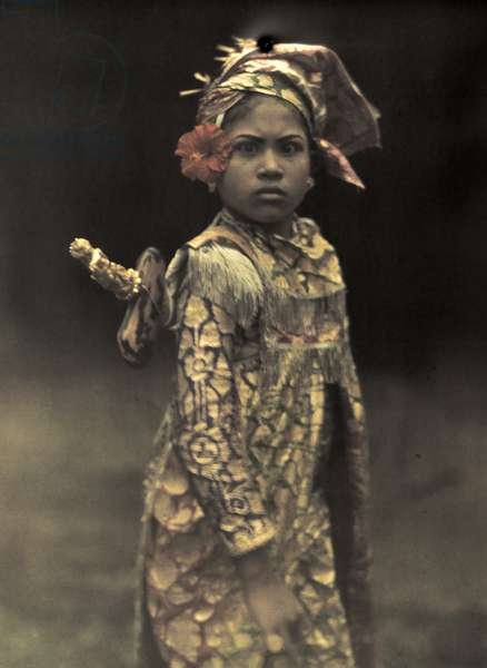 A child performer dresses in costume for a role in an island play, Bali, Indonesia, 1928 (autochrome)