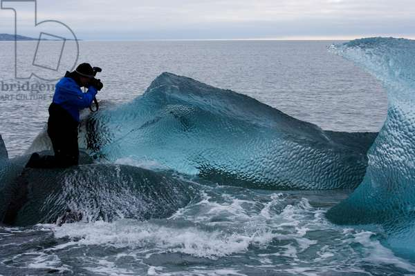 A photographer takes images of dimpled glacier ice formed by currents (photo)