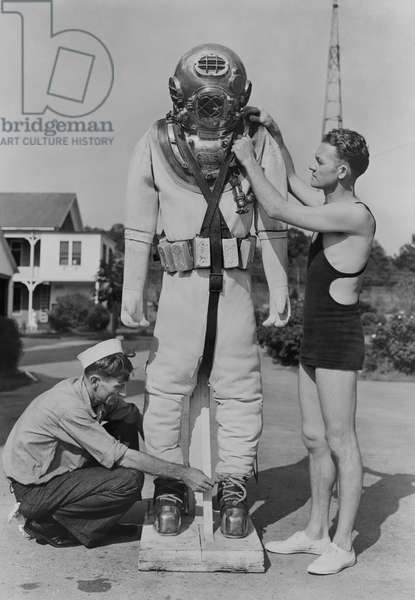 Seamen adjusting a standard Navy diving dress at the Submarine Base in New London, Connecticut, New London, Connecticut, USA, 1935 (b/w photo)