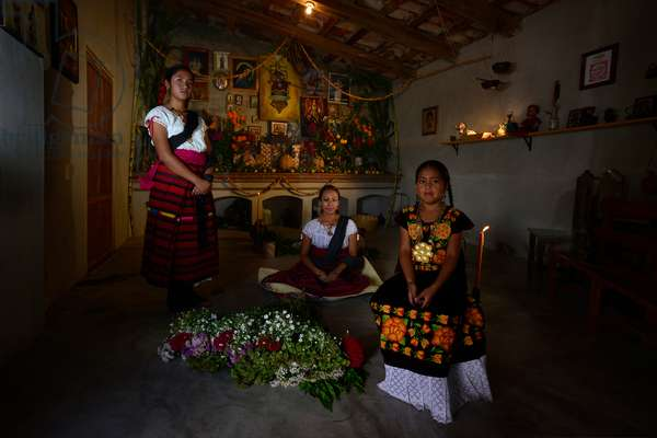 Women sit in front of the Day of the Dead Altar in their home (photo)
