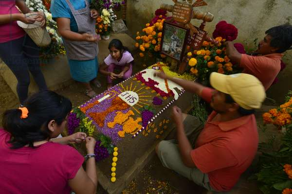 People decorate a grave with flowers for Day of Dead celebration at the San Antonino cemetery (photo)