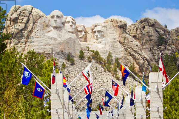 Low angle view of the sculpted images of American presidents Washington, Jefferson, Theodore Roosevelt, and Lincoln, along with flags of the 50 United States at Mount Rushmore (photo)