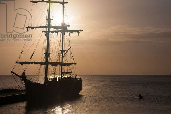 A two masted brig with furled sails docked in the harbor of George Town (photo)
