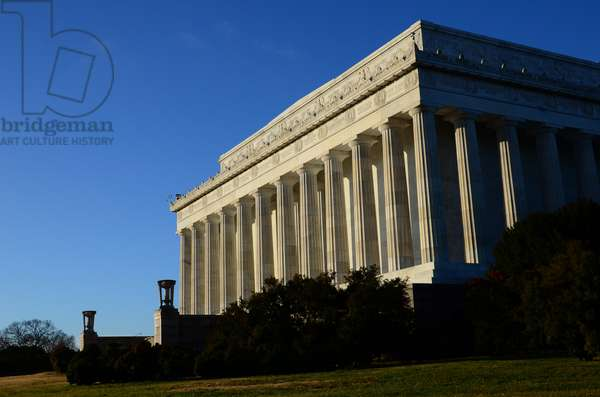 A clear blue sky and morning light illuminate the Lincoln Memorial