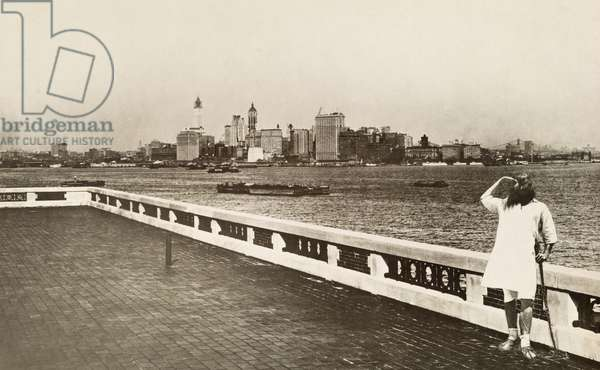 A Russian Hebrew immigrant stands before the New York City skyline, Ellis Island, 1917 (b/w photo)