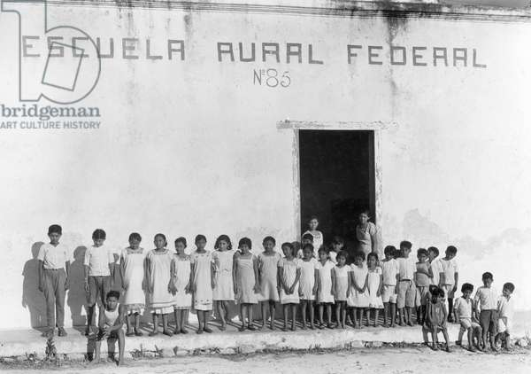Yucatan children stand outside a federally funded school in Piste, Piste, Yucatan, Mexico, 1936 (b/w photo)
