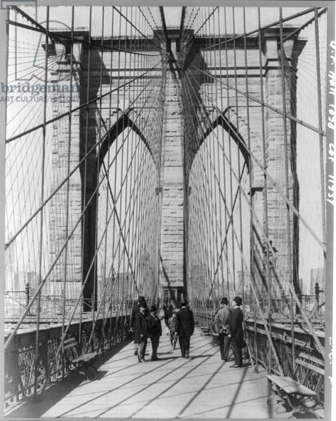 A photograph of people standing and walking on the Brooklyn Bridge promenade (photo)