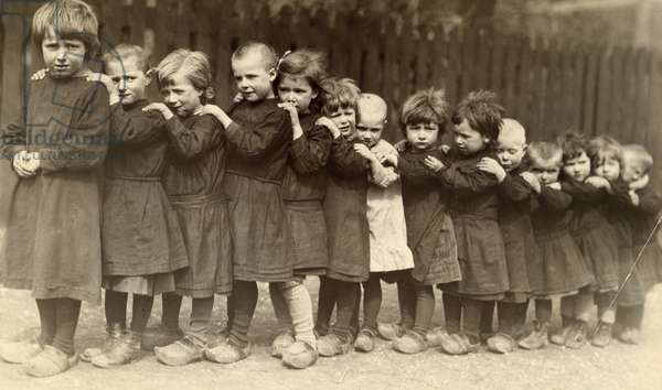 Young children, affected by WWI, align by height, Europe, 1917 (b/w photo)