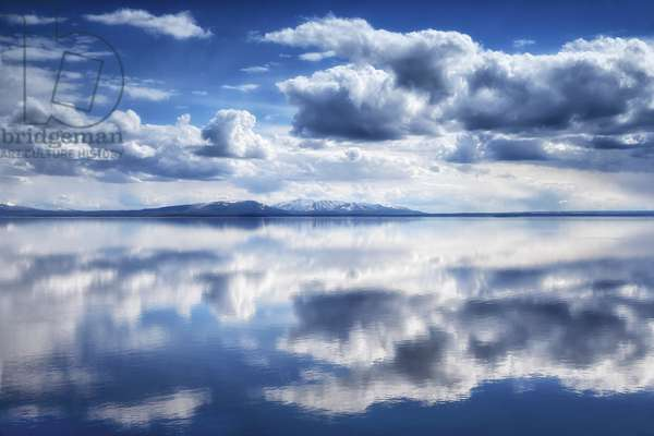 Yellowstone Lake reflects a perfect mirror-image of the clouds on a sunny day (photo)