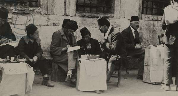The public letter writer helps with letters for illiterate people, Turkey, 1922 (b/w photo)
