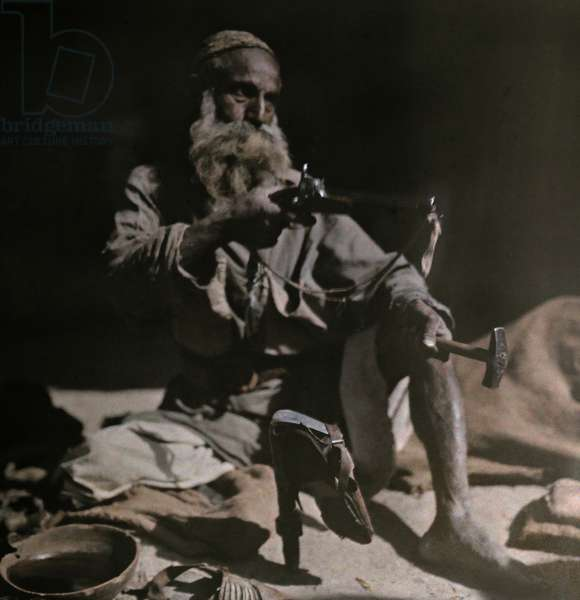An elderly man makes leather shoes with his toold, Jamrud, India, 1923 (autochrome)