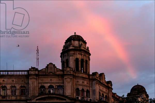 A rainbow arches over a colonial era building on Park Street, now renamed Mother Teresa Sarani (photo)