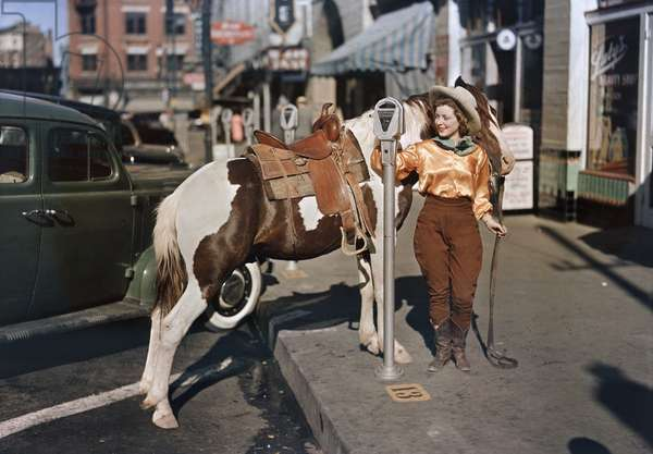 A cowgirl puts a nickel in an El Paso parking meter to hitch her pony, El Paso, Texas, 1939 (photo)