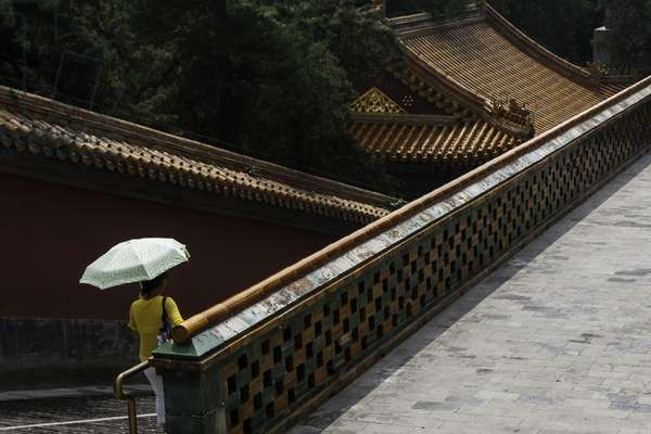A woman with an umbrella walking down an ornate stairway at the Summer Palace (photo)