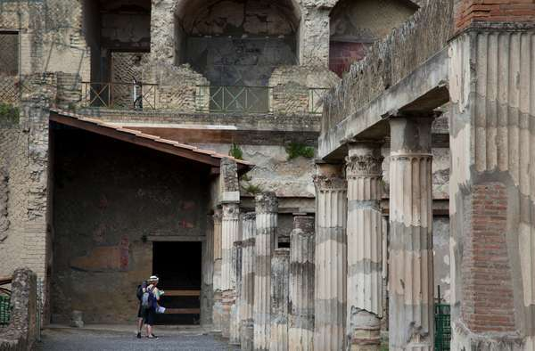 Tourists among columns in the House of the Gem in Herculaneum (photo)
