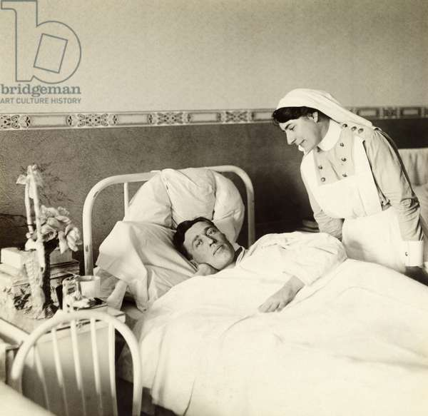 A nurse cares for a wounded WWI Canadian soldier lying in bed, Spadina Military Hospital, Toronto, Canada, 1917 (b/w photo)