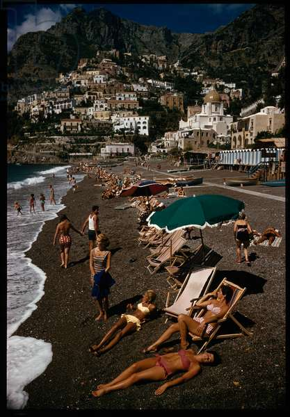 Sunbathers lounge on a pebbled beach by whitewashed houses on a cliff, Positano, Italy, 1959 (photo)