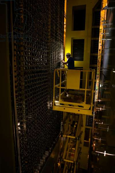 Worker attaches fiber optics to the detector's photo multiplier tube (photo)