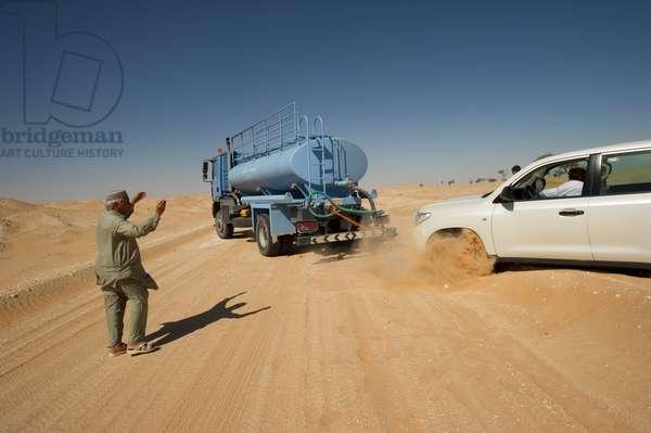A blue water truck pulls a car out of the sand near Al Manader near the Saudi Arabia border in the Rub' al Khali, the Empty Quarter, Oman (photo)
