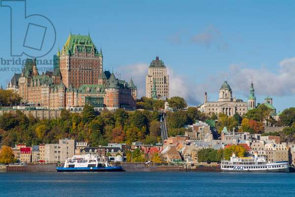 The iconic Chateau Frontenac dominates the skyline of Quebec City as seen from the Saint Lawrence River below