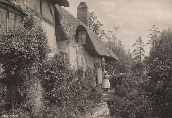A woman stands outside Anne Hathaway's cottage, Stratford-on-Avon, 1922 (b/w photo)
