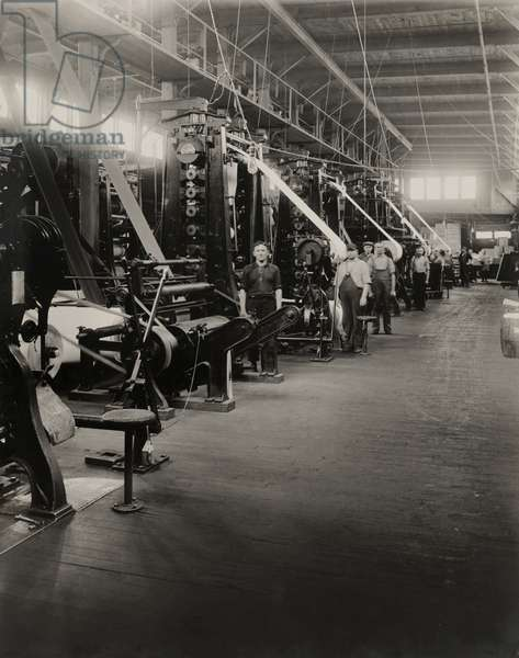Workers operating the reels of finished paper tp process the print, Lawrence, Massachusetts, 1920 (b/w photo)