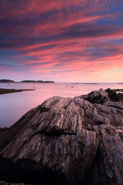 A man fishing off of the rocky coast of Maine at sunset (photo)