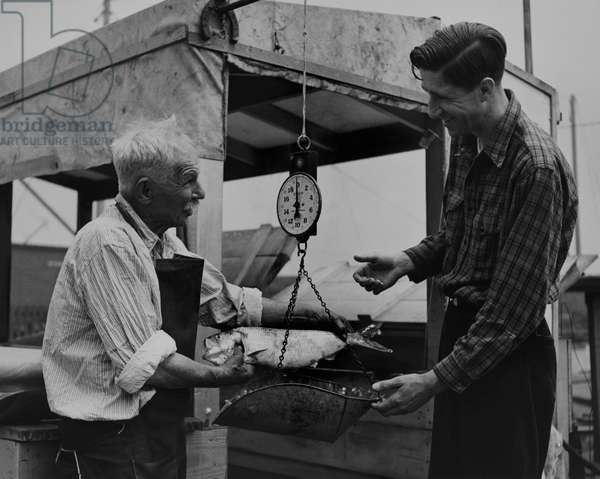 A fishmonger weighs a shad for a customer, Edgewater, New Jersey, 1942 (b/w photo)