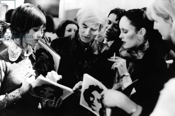 Andy Warhol signing autographs outside his exhibition at the Tate Gallery, London, February 1971 (b/w photo)