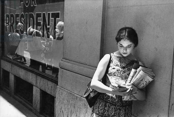 Young woman holding a photograph of Robert F. Kennedy after his assassination, 1968 (b/w photo)