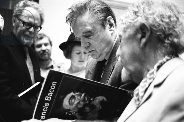 Francis Bacon signs autographs at his Tate Retrospective exhibition, 1985 (b/w photo)