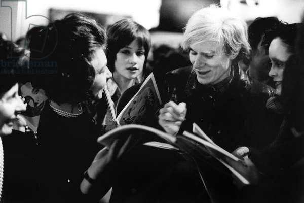 Andy Warhol signing autographs outisde his exhibition at the Tate Gallery, London, February 1971 (b/w photo)