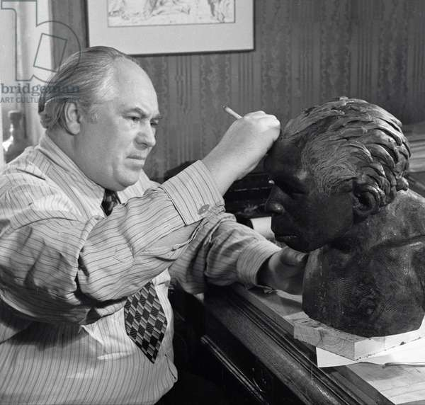 Soviet anthropologist and sculptor Mikhail Gerasimov reconstructing head of a Neanderthal, 1954 (b/w photo)
