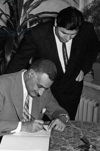 Egypt's President Gamal Abdel Nasser, left, signs in the Armored Troops Academy Visitors' Book, 1965 (b/w photo)