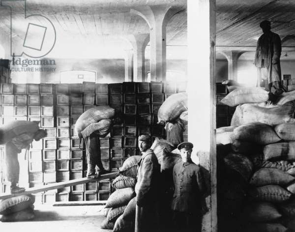 Petrograd residents unload food from U.S. ship for famine victims in the Volga region, 1920 (b/w photo)