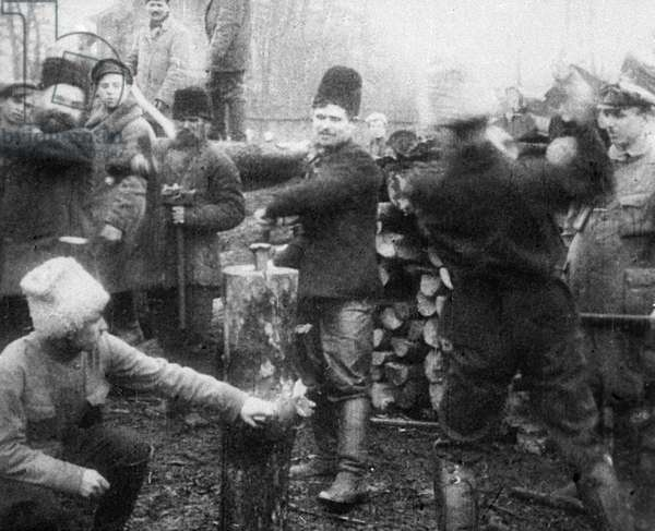 Volunteers cutting firewood during subbotnik in Kremlin, 1920 (b/w photo)