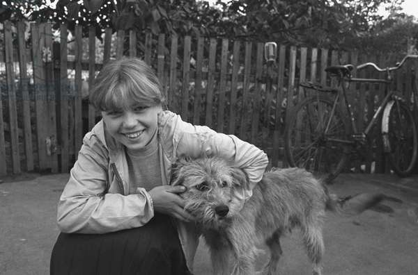 A girl with a dog in a new village built for people evacuated from the 30-km exclusion zone around the Chernobyl power plant, 1986 (photo)
